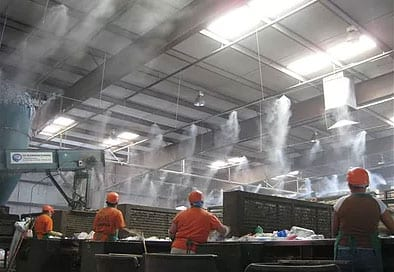 Employees in a waste management facility beneath Custom Fog Designs mist and fog system